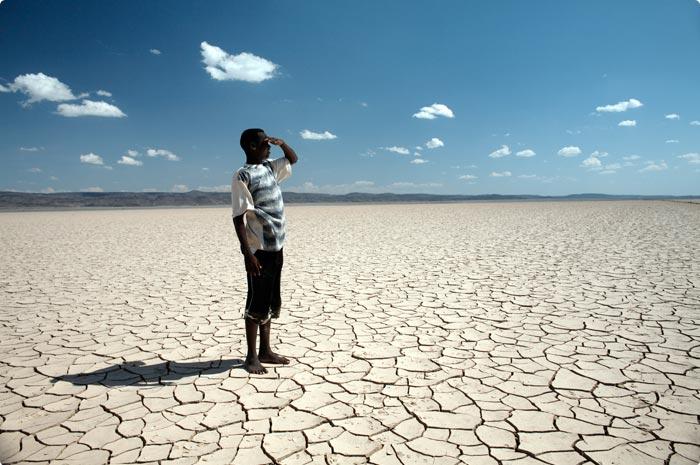 Hombre negro mirando el desierto seco