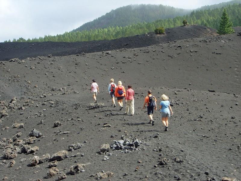 Personas haciendo ruta por un volcán